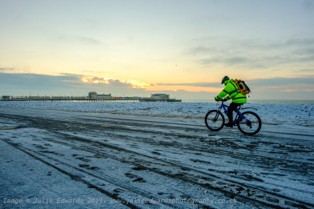 A cyclist rides along the icy promenade as Snow hits the South East of the UK on Friday 1 February 2019